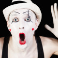mime in striped gloves and white hat on black background